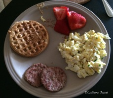 Toaster waffle, scrambled eggs, sausage, strawberries.